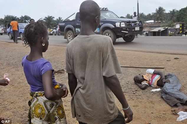 Modern-day lepers: In Liberia, suspected Ebola patients like this man (right) are seen most days lying near busy streets -- with most people terrified of touching them